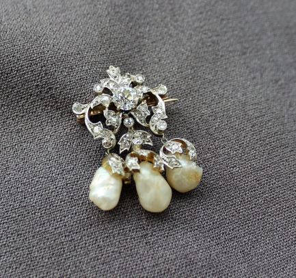 A Victorian diamond and natural shaped pearl set brooch, the central round old cut diamond, approximately 0.5 of a carat surrounded by old cut diamonds to a leaf setting, the natural shaped pearls suspended beneath, to a yellow and white metal setting 23mm wide x 37mm high. Sold for £800 at Anthemion Auctions