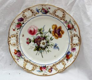 A Nantgarw plate, circa 1818-20, decorated in London, probably in the Bradley workshop. with an elaborate central floral spray with an anemone and rose flanked by insects in flight, a bright blue enamel line around the cavetto, the 'C' scroll border moulded with floral garlands picked out in gold, painted with floral sprays, impressed Nant-Garw C.W., 24.5cm diameter. Sold for £2,800 at Anthemion Auctions