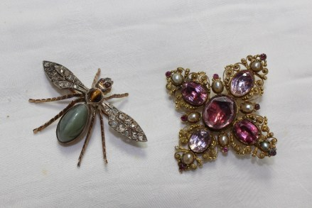A yellow and white metal brooch in the form of a fly set with diamond wings, ruby eyes, tigers eye and hardstone body, together with a paste set brooch. Sold for £340 at Anthemion Auctions