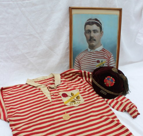 """Lancashire Northern Rugby Football Union - A red and white rugby jersey with Lancashire N.R.U rose embroidered badge, together with an 1899 maroon velvet cap with rose and shield embroidered emblem, made by Joe Nicholl & J T Brown, Halifax, embroidered with the initials """"H.K."""", a 15ct yellow gold medallion cast with three lions on shield on a leaf cartouche, """"Presented by The Lancashire County Football Union"""" on the front, the reverse """"Northern Union County Championship won by Lancashire, H K Kruger, Half Back"""", hallmarked Birmingham, 1899, approximately 16 grams, and a hand coloured photograph of Henry Kruger wearing the jersey and cap. Henry Kruger was born in 1878 in Manchester but of Welsh parentage. His parents returned to Cardiff. He played rugby as half back for Llwynypia and then """"went north"""" and played for Rochdale Hornets and Hull Kingston Rovers. The medal, jersey and cap were won for Lancashire against Yorkshire in 1899, part of the Rugby League """"War of Roses"""" series. Sold for £900 at Anthemion Auctions"""
