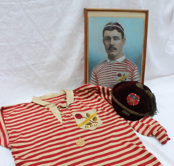 "Lancashire Northern Rugby Football Union - A red and white rugby jersey with Lancashire N.R.U rose embroidered badge, together with an 1899 maroon velvet cap with rose and shield embroidered emblem, made by Joe Nicholl & J T Brown, Halifax, embroidered with the initials ""H.K."", a 15ct yellow gold medallion cast with three lions on shield on a leaf cartouche, ""Presented by The Lancashire County Football Union"" on the front, the reverse ""Northern Union County Championship won by Lancashire, H K Kruger, Half Back"", hallmarked Birmingham, 1899, approximately 16 grams, and a hand coloured photograph of Henry Kruger wearing the jersey and cap. Henry Kruger was born in 1878 in Manchester but of Welsh parentage. His parents returned to Cardiff. He played rugby as half back for Llwynypia and then ""went north"" and played for Rochdale Hornets and Hull Kingston Rovers. The medal, jersey and cap were won for Lancashire against Yorkshire in 1899, part of the Rugby League ""War of Roses"" series. Sold for £900 at Anthemion Auctions"