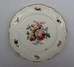 A Nantgarw porcelain plate painted to the centre with a spray of garden flowers, the border painted with fruit between moulded edge and gilt scalloped rim, impressed 'NANT-GARW C.W.', 22cms diameter. Sold for £900 at Anthemion Auctions
