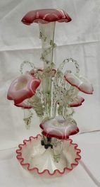 Victorian opaque glass and red rimmed epergne, with a central trumpet, three other trumpets, spiral glass sticks and similar baskets on a wave form base, 53cm high