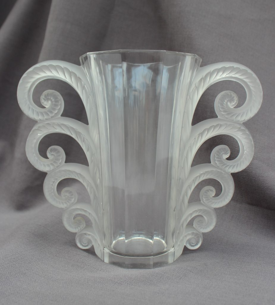 A Lalique Beauvais vase with a tapering decagon cylindrical body with five graduated scrolling leaves to each side, stencilled LALIQUE FRANCE to the base, approximately 19.3cm tall x 24.5cm wide. Sold for £700 at Anthemion Auctions