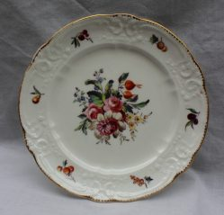 A Nantgarw porcelain plate painted to the centre with a spray of garden flowers, the border with individual fruit to a moulded rim and scalloped gilt edge, impressed 'NANT-GARW C.W', 22cms diameter. Sold for £900 at Anthemion Auctions