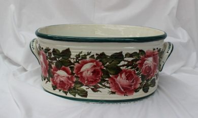 A Wemyss pottery footbath, painted with roses and leaves, with a broad green rim, and a ribbed oval body with carrying handles, a T Goode & Co oval printed mark to the base, 43cm wide (not including handles) x 32cm deep x 19.5cm high. Sold for £880 at Anthemion Auctions