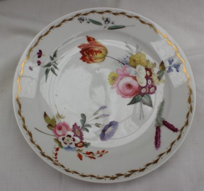 A 19th century porcelain plate in the Swansea style, painted with sprays of garden flowers, the border with an interlaced gilt edge, 22.5cm diameter. Sold for £210 at Anthemion Auctions