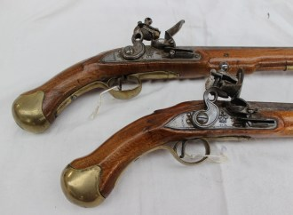 "A pair of long sea service flintlock pistols with tapering barrel, border-engraved lock with ""Tower"" and ""GR"" crowned, rounded pan, full stock, brass mounts, steel belt hook on one, and brass-tipped ramrod, 49 cm overall. Sold for £2,400 at Anthemion Auctions"