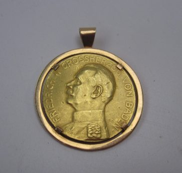 A yellow metal coin on the one side is a portrait in profile of Friedrich II Grossherzog Von Baden, to the other side Fur Verdienst, in a yellow metal slip mount, approximately 22 grams Sold for £270 at Anthemion Auctions