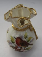 A Worcester porcelain vase in the form of a tied bag, decorated with a robin on a holly branch impressed and printed mark, 10 cms high. Sold for £65 at Anthemion Auctions