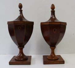 A matched pair of George III mahogany tea caddies of urn shape with acorn finials and panelled lids on spreading foot and a geometrically inlaid square base, 26cm high. Sold for £2,900 at Anthemion Auctions