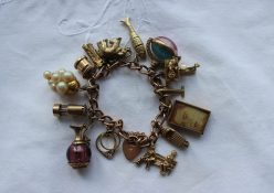 A 9ct yellow gold charm bracelet set with numerous charms including figures on a bench, speed boat, aeroplane, baby on a scales, fish, elephant, train, postbox, miners lamp etc, overall approximately 56 grams. Estimates of £500 - 800