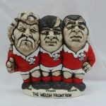 A John Hughes pottery Grogg 'The Welsh Front Row, Price, Windsor and Faulkner', signed and dated 1991 to the base, 16.5cm high. Sold for £190 at Anthemion Auctions