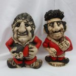 A John Hughes pottery Grogg 'Wales Forever', in a red jersey with the No.3 on the reverse, 22cm high together with another Grogg in a red jersey with the No.9 on the reverse, 21cm high. Sold for £200 at Anthemion Auctions