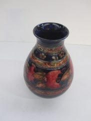 """A Moorcroft """"Pomegranate"""" pattern baluster vase with banded floral decoration to a blue ground. Impressed and painted marks. 18 cms high. Sold for £1,850 at Anthemion Auctions"""