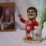 """A Richard Hughes resin grogg of Max Boyce, the figure wearing a rosette with the Prince of Wales feathers and holding a leek, signed by Max Boyce and Richard Hughes dated '99, 23cm high together with a Variety club of Great Britain programme, """"A tribute to Max Boyce at the Hilton on 21st August 1999. Sold for £150 at Anthemion Auctions"""
