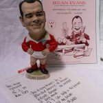 """A John Hughes resin grogg of Ieuan Evans, the figure wearing a Wales rugby kit, signed by Ieuan Evans and John Hughes dated '99, 23cm high together with a Variety club of Great Britain programme, """"A tribute dinner to Ieuan Evans at the Marriott on 17th February 1999. Sold for £150 at Anthemion Auctions"""