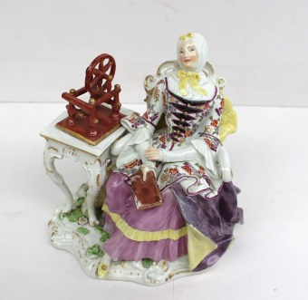 A Meissen porcelain figure group, modelled as an elegant lady seated in an armchair, a book in her right hand, a spinning wheel on the table beside her, raised on a scroll moulded base, crossed swords in underglaze blue to base, 16cm high. Sold for £1,200 at Anthemion Auctions