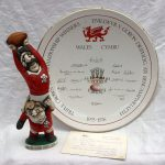 "A John Hughes grogg titled ""Under every great lock......Theres a good prop"", signed to the underside and dated 1989, 27.5cm high, together with a Ra pottery Ltd ""The Grand Slam Commemorative Bowl, a Garrick Ward design, Bowl number: 222, 32.5cm diameter, with a certificate. Sold for £160 at Anthemion Auctions"