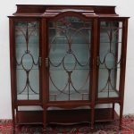 An Edwardian mahogany display cabinet, the stepped caddy top above three glass doors and glass sides with decorative glazing bars on square tapering legs and spade feet united by an undertier, 134 cm wide by 40 cm deep by 150 cm high. Sold for £580 at Anthemion Auctions