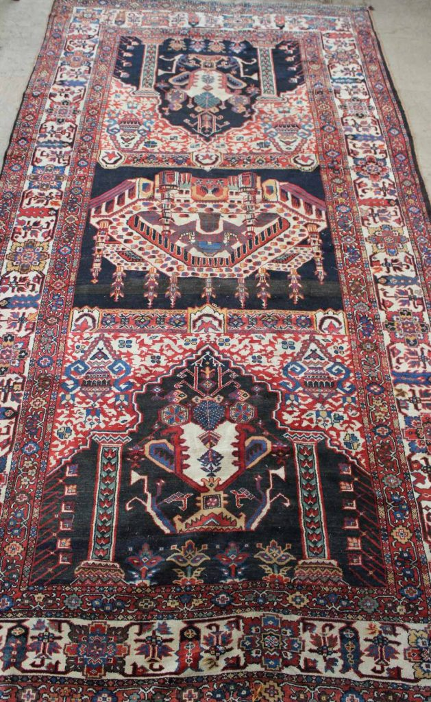 An Islamic rug, the centre decorated with a temple with borders of crescents and stars, with numerous stylised floral borders and guard strips, 220 cm wide by 440 cm. Sold for £980 at Anthemion Auctions