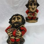 """A John Hughes Grogg, titled """"Gareth Owen Edwards"""" in a Welsh rugby shirt with No.9 to the reverse, inscribed """"John Hughes Wales, 1977"""" faint Gareth Edwards signature to the base, 24.5cm high together with a pottery wall plaque of a rugby player, 33cm high. Sold for £280 at Anthemion Auctions"""