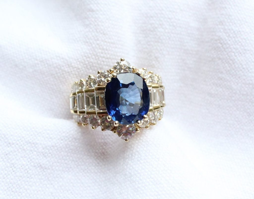 A sapphire and diamond ring, the central oval sapphire approximately 11mm x 9mm, with ten baguette cut diamonds (five stepped to each side) ranging from approximately 0.3 to 0.1 of a carat, with twenty two round brilliant cut diamonds (eleven to each side) ranging from approximately 0.2 to 0.05 of a carat to a yellow metal claw setting and shank, ring size approximately K 1/2, (with an East West arts and gems certificate stating 1. Ring real saphire 6.06crt, real baguets 1.79crt, round diamond 1.84crt, U.S. Dollars eleven thousand). Estimates of £3,000 - 4,000