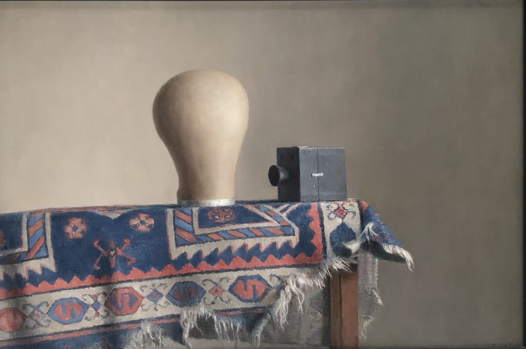 Harry Holland - Still Life study of a milliners hat block, camera and rug. Oil on board, Signed 42.5 x 63.5cm