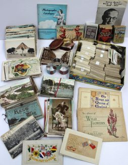A collection of circa 300 postcards including scenes of the suez, Kuala Lumpa, Giza, Hong Kong, Singapore, Sierra Leone, Barry, Birkenhead, Plymouth, Swansea, Bristol, comic cards, World War 1 cards, playing cards, a collection of cigarette cards, copper tokens etc. Sold for £340 at Anthemion Auctions