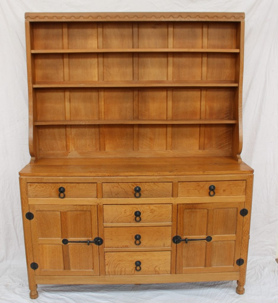 """A Robert Thompson of Kilburn """"Mouseman"""" oak dresser and rack, with a blind carved scallop frieze above a panelled back and three shelves, the dresser base having three drawers across and three graduated drawers to the centre flanked by a four-indented panel door to either side, with iron latch and ring handles, back plates and hinges, on short octagonal turned feet carved in relief with a mouse. 152.5cm wide x 45.5cm deep x 194cm high. Sold for £2,000 at Anthemion Auctions"""