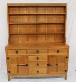 "A Robert Thompson of Kilburn ""Mouseman"" oak dresser and rack, with a blind carved scallop frieze above a panelled back and three shelves, the dresser base having three drawers across and three graduated drawers to the centre flanked by a four-indented panel door to either side, with iron latch and ring handles, back plates and hinges, on short octagonal turned feet carved in relief with a mouse. 152.5cm wide x 45.5cm deep x 194cm high. Sold for £2,000 at Anthemion Auctions"