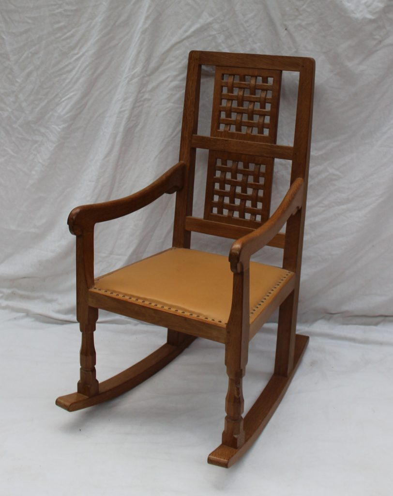 """A Robert Thompson of Kilburn """"Mouseman"""" oak rocking chair with a double lattice back and tan leather seat, with original receipt dated 1989. Sold for £700 at Anthemion Auctions"""