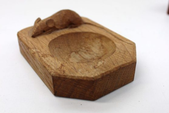 "A Robert Thompson of Kilburn ""Mouseman"" oak pin tray, with trademark carved mouse, 10cm long, together with a brass bound treen snuff box. Sold for £40 at Anthemion Auctions"