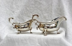 "A graduated pair of Edward VII silver sauce boats, with a gadrooned edge and leaf capped scrolling handle, on four shell feet, initialled ""CPM"", Chester, 1909, Barker Brothers, approximately 674 grams. Sold for £230 at Anthemion Auctions"