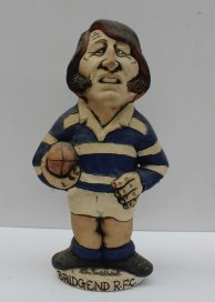 A John Hughes pottery Grogg of J.P.R. Williams in Bridgend kit with a ball under his arm and number 15 on the reverse, the base incised 'Bridgend R.F.C', signed by John Hughes to the base, 24.5cm high