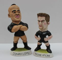 A World of Groggs resin model of Jonah Lomu in a black jersey with arms folded and number 11 on the back, signed by Richard Hughes, 16.5cm high together with another of Richie McCaw 12.5cm high. Sold for £110 at Anthemion Auctions
