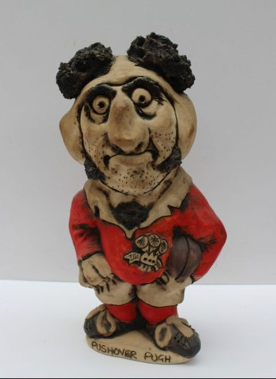"A John Hughes pottery Grogg titled ""Pushover Pugh"", in a red Welsh jersey with the No.3 on the reverse, signed to the base, 32.5cm high. Sold for £150 at Anthemion Auctions"