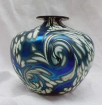 A Norman Stuart Clarke studio glass vase, with swirling white decoration to a irridescent blue ground, signed and dated 90 to the base, 13.5cm high. Sold for £50 at Anthemion Auctions