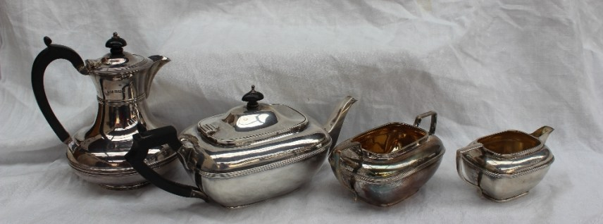 An Edward VII silver three piece tea set of flattened rectangular form, Birmingham, 1906, William Devenport, together with a George V silver hot water pot, approximately 1430 grams