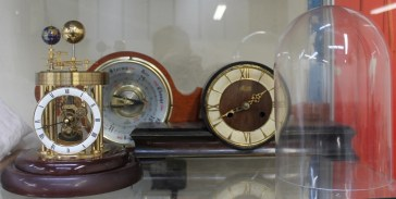 A Frank Hermle Astrolabium 2000 celestial clock, under a glass dome, together with a Hermle mantle clock and an Aneroid barometer