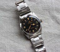 A Gentleman's Rolex Oyster Perpetual Explorer wristwatch, with a black dial, luminous markers, 3,6 & 9, with Mercedes yellow metal minute hand, No.268225, the movement marked N713730, 1030 calibre movement, inside back cover and between the lugs marked 6610, on a stainless steel Rolex bracelet strap with a Guarantee purchased from M Mansour & Sons, Aden on December 27th 1957. Sold for £8,200 at Anthemion Auctions