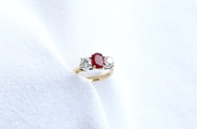 A ruby and diamond ring, the central oval mixed cut strong red transparent natural ruby 7.55mm x 5.57mm x 2.91mm measuring 1.12 carats flanked by two round brilliant cut diamonds approximately 0.5 carats, colour E, Clarity VS2 and 0.51 carats, colour E, Clarity VS1 to a yellow and white metal claw setting and 18ct yellow gold shank, approximately 4.8 grams, size L and a half. Sold for £2,100 at Anthemion Auctions