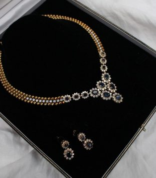 An 18ct yellow gold sapphire and diamond necklace set with twenty two round brilliant cut diamonds to the body of the three strand necklace, the base set with twelve sapphire and diamond clusters of graduating sizes together with a pair of matching sapphire and diamond earrings, 41cm long, approximately 80.5 grams. Sold for £4,500 at Anthemion Auctions