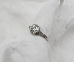 A solitaire diamond ring, the cushion cut diamond approximately 1ct with three diamonds to each shoulder to a platinum claw setting and shank size N 1/2. Sold for £2,700 at Anthemion Auctions
