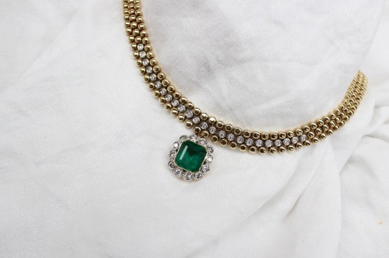 An 18ct yellow gold necklace set with an emerald and diamond pendant, the three strand necklace set with twenty four round brilliant cut diamonds, each approximately 0.05 of a carat, the pendant with a rectangular emerald measuring approximately 10mm x 11mm surrounded by twelve round brilliant cut diamonds, each approximately 0.10 of a carat, 43.5cm long and approximately 78 grams. Sold for £2,250 at Anthemion Auctions