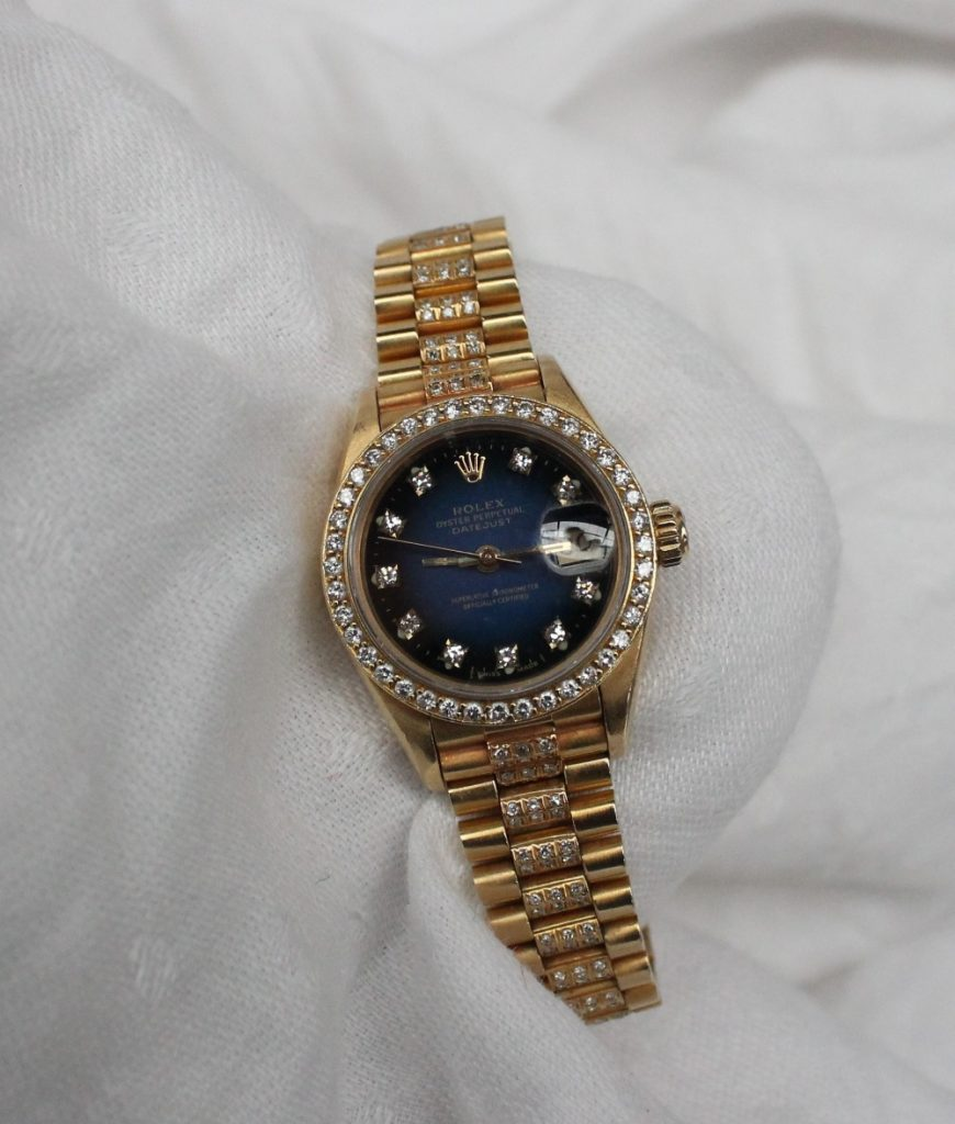 Lot 101 - Estimates: £3,000 - 5,000. A Lady's 18ct yellow gold diamond set Rolex oyster perpetual datejust wristwatch, with a blue dial, diamond set markers, diamond set bezel and diamond set strap, overall approximately 69.7 grams, box, no papers CONDITION REPORT: Provenance: from a private vendor