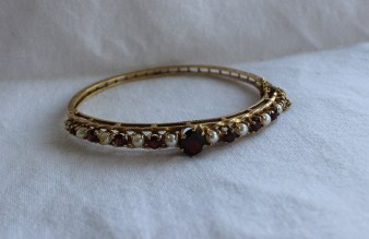 Lot 49 - Estimates: £200 - 300. A Garnet and pearl set hinged bangle, with a large oval garnet and eight circular garnets and ten pearls, to a 9ct yellow gold setting, approximately 16 grams