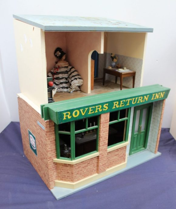 """Lot 642 - Estimates: £50 - 80. Dolls House - """"Rovers Return Inn"""" fitted out as bar with figures, piano etc, together with a house interior"""