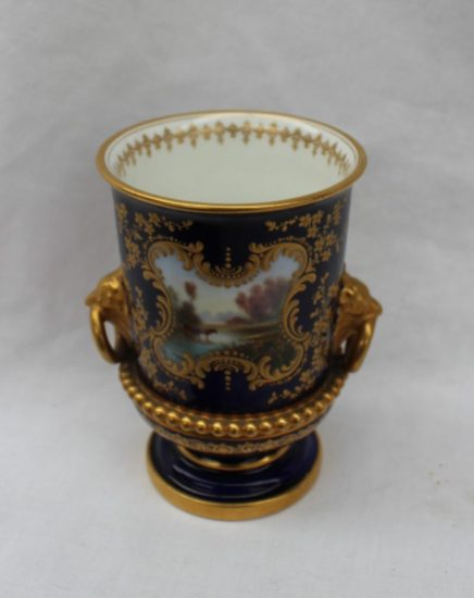 A Royal Worcester twin handled vase of urn shape painted with cattle in a stream signed by Harry Davis, to a blue ground with gilt highlights, green printed mark 10.5cm high. Sold for £350 at Anthemion Auctions