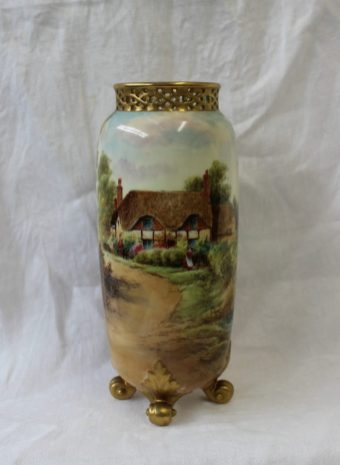 A Royal Worcester porcelain circular tall vase with reticulated top, on four scrolled feet, shape No. G42, painted with a figure outside a thatched cottage, a small pond nearby, 'Ripple', and gilt, by Raymond Rushton, date code for 1929, 22.4 cms high. Sold for £130 at Anthemion Auctions